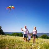 Famille jouant avec le cerf-volant Photo stock