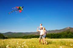 Famille jouant avec le cerf-volant Photographie stock libre de droits