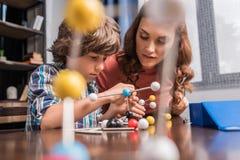Famille jouant avec le modèle d'atomes Images libres de droits