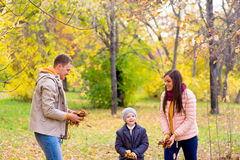 Famille jouant avec le parc d'automne de feuilles Photos libres de droits
