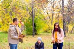 Famille jouant avec le parc d'automne de feuilles Photographie stock libre de droits