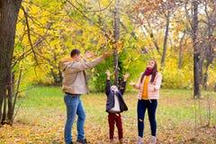 Famille jouant avec le parc d'automne de feuilles Image stock