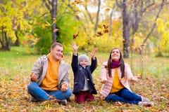 Famille jouant avec le parc d'automne de feuilles Image libre de droits