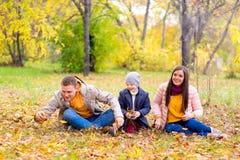 Famille jouant avec le parc d'automne de feuilles Images libres de droits
