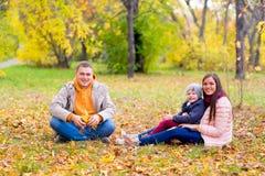 Famille jouant avec le parc d'automne de feuilles Photo stock