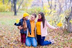 Famille jouant avec le parc d'automne de feuilles Photographie stock