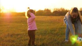 Famille jouant avec le petit enfant par la boule des enfants en parc au coucher du soleil la m?re joue avec peu de fille dans la  banque de vidéos