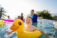 Famille jouant dans une piscine photographie stock libre de droits