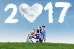 Famille jouant la bulle de savon avec le nuage 2017 Photographie stock libre de droits