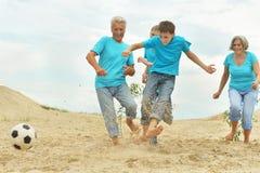 Famille jouant le football sur une plage photo libre de droits