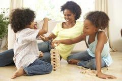 Famille jouant le jeu à la maison images stock