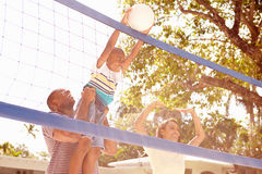 Famille jouant le jeu du volleyball dans le jardin Photographie stock libre de droits