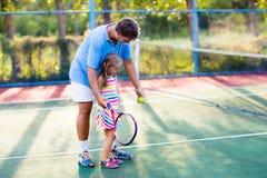 Famille jouant le tennis sur la cour extérieure photos stock