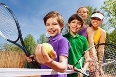 Famille jouant le tennis tenant les raquettes et la boule Images libres de droits