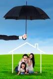 Famille jouant sous l'icône et le parapluie de maison Photos stock