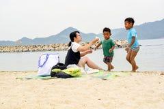 Famille jouant sur la plage sous le ciel ensoleillé Image libre de droits