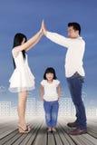 Famille jouant une maison avec leur fille Photographie stock