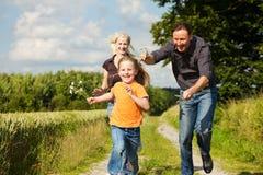 Famille jouant à une promenade Images libres de droits