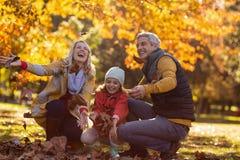 Famille joyeuse au parc pendant l'automne photographie stock libre de droits