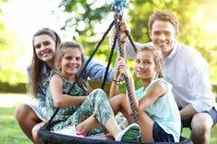 Famille joyeuse ayant l'amusement sur le terrain de jeu photos libres de droits