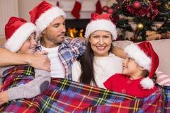 Famille joyeuse dans le chapeau de Santa étreignant sous la couverture Photos stock