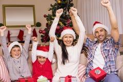 Famille joyeuse dans le chapeau de Santa encourageant sur le divan Images stock