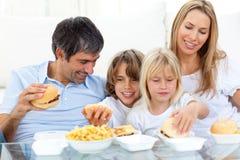 Famille joyeuse mangeant des hamburgers photo stock