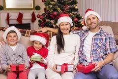 Famille joyeuse posant avec des cadeaux sur le divan Image stock