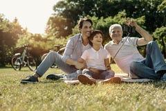 Famille joyeuse prenant des photos et le sourire Images libres de droits