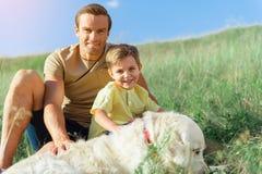 Famille joyeuse se reposant en nature avec le chien Photos stock