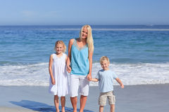 Famille joyeux marchant sur la plage Photos stock