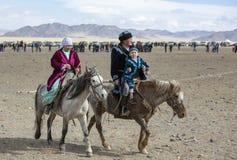 Famille kazakh voyageant sur leurs chevaux photographie stock libre de droits