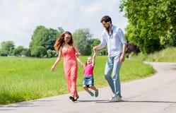 Famille laissant l'enfant voler dans la promenade d'été Photos stock