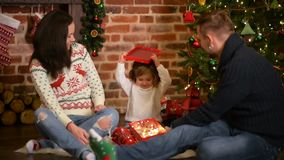 Famille le réveillon de Noël à la cheminée Parents et petit enfant ouvrant des présents de Noël Enfants avec des boîte-cadeau viv banque de vidéos