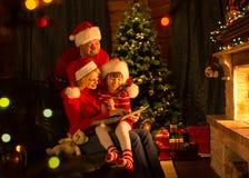 Famille lisant un livre par un arbre de Noël dans confortable Photos stock