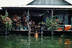 famille locale appréciant un après-midi tranquille à leur maison de maison d'échasse tout en rasant et ayant un bain image stock