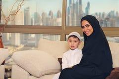 Famille, mère Arabe et fils s'asseyant sur le divan dans leur salon Image stock