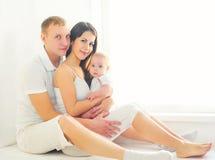 Famille, mère et père heureux avec la maison de bébé dans la chambre blanche images stock