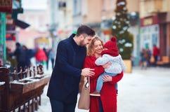 Famille, mère, père heureux et bébé marchant par la rue neigeuse de ville d'hiver Photo stock