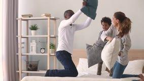 Famille mélangée heureuse d'appartenance ethnique ayant le combat d'oreiller sur le lit banque de vidéos