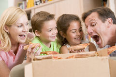 Famille mangeant de la pizza ensemble images stock