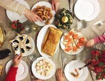 Famille mangeant des fruits de mer, des tapas et plus sur Noël Photographie stock libre de droits