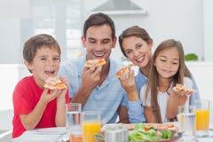 Famille mangeant des tranches de pizza Photographie stock