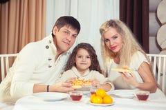 Famille mangeant le dîner à une table de salle à manger, table ronde, pizza, orange, maison faite de bois Images libres de droits