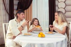 Famille mangeant le dîner à une table de salle à manger, table ronde, pizza, orange, maison faite de bois Image stock