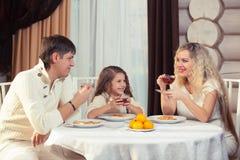 Famille mangeant le dîner à une table de salle à manger, table ronde, pizza, orange, maison faite de bois Photo stock