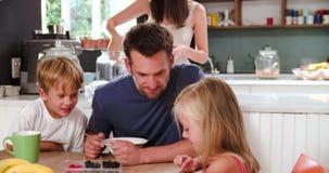 Famille mangeant le petit déjeuner dans la cuisine ensemble banque de vidéos