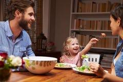 Famille mangeant un dîner à une table de salle à manger photo stock
