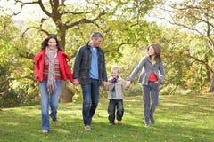 Famille marchant à l'extérieur par le stationnement photos stock