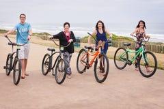 Famille marchant avec des bicyclettes et regardant l'appareil-photo Image libre de droits